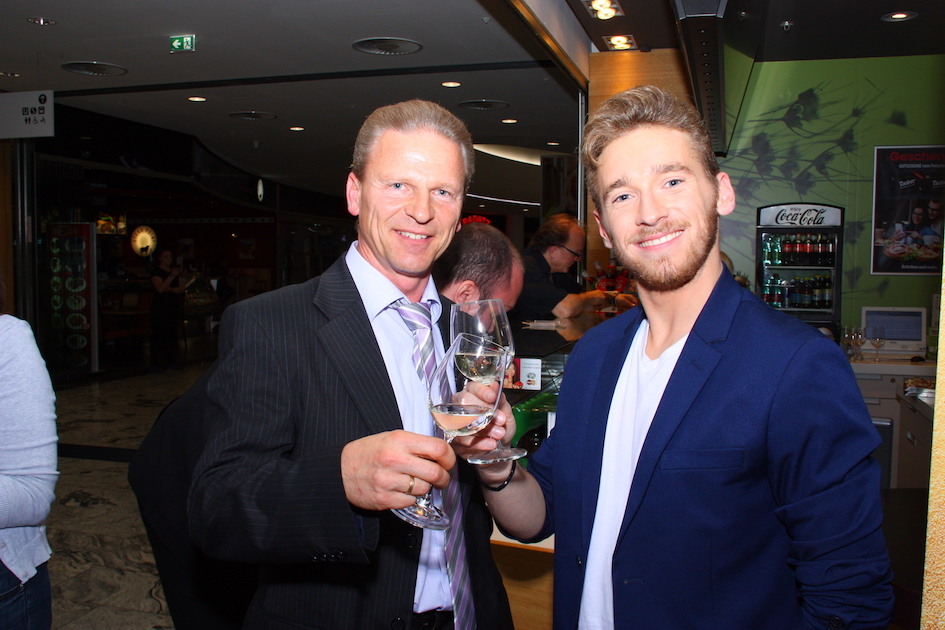 Josef Weiß und Nathan Trent stoßen mit Wein von Winzerhof Weiß an